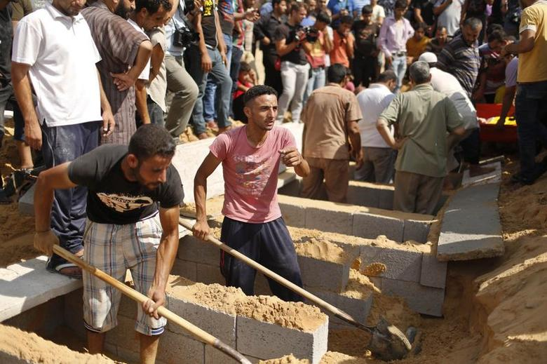 Palestinians prepare the graves for eight members of the Abu Jarad family, including three children, who medics said were killed by an Israeli tank shell, at a cemetery in Beit Lahiya in the northern Gaza Strip July 19, 2014. REUTERS/Suhaib Salem