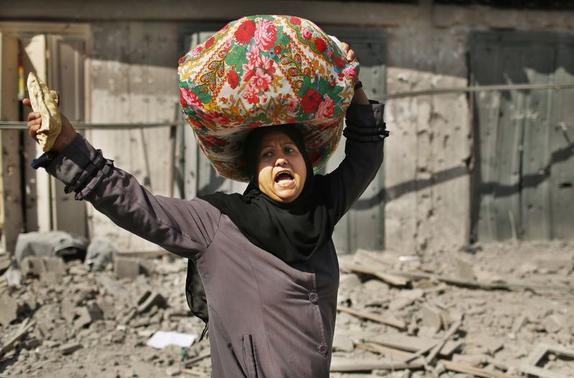 A Palestinian woman reacts as she carries her belongings from her destroyed house in Beit Hanoun town, which witnesses said was heavily hit by Israeli shelling and air strikes during an Israeli offensive, in the northern Gaza Strip July 26, 2014.  REUTERS/Suhaib Salem