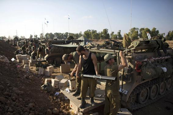 Israeli soldiers prepare armoured personnel carriers (APCs) at a staging area outside the northern Gaza Strip July 27, 2014.  REUTERS-Ronen Zvulun