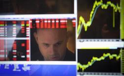 Un operador reflejado en la pantalla de su ordenador en la bolsa de Wall Street en Nueva York, oct 14 2013. Las acciones caían el lunes en la bolsa de Nueva York, luego de que el mercado viera los débiles datos de ventas pendientes de casas y del sector de servicios como señales de un deterioro de las condiciones económicas en Estados Unidos, lo que provocó que el índice S&P 500 retrocediera bajo su nivel de apoyo.    REUTERS/Carlo Allegri