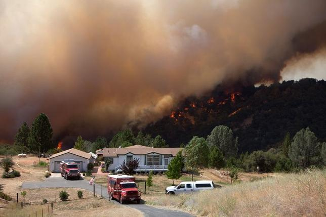 Firefighters protect an evacuated home while the fast-moving wildfire called ''Sand Fire'' burns behind, near Plymouth, California July 26, 2014.   REUTERS/Max Whittaker