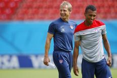 The U.S. national soccer team head coach Juergen Klinsmann (L) smiles as his team, including midfielder Julian Green, stretch during a training session at the Pernambuco arena in Recife June 25, 2014.    REUTERS/Brian Snyder