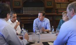 Президент США Барак Обама (слева), премьер Британии Дэвид Кэмерон (в центре) и канцлер Германии Ангела Меркель на саммите G8 в Северной Ирландии 17 июня 2013 года. Лидеры США и Евросоюза в понедельник вечером договорились ввести новые санкции в отношении финансового, оборонного и энергетического секторов России после катастрофы пассажирского лайнера на востоке Украины, охваченном боями правительственных войск с промосковскими сепаратистами. REUTERS/Stefan Rousseau/pool