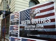 """Un afiche en contra de los inversores """"holdouts"""" en una calle de Buenos Aires, jun 18 2014.  Los costos de asegurar la deuda de Argentina subieron el martes a máximos en seis semanas por el temor a que el país pueda caer en un default esta semana.   REUTERS/Enrique Marcarian"""