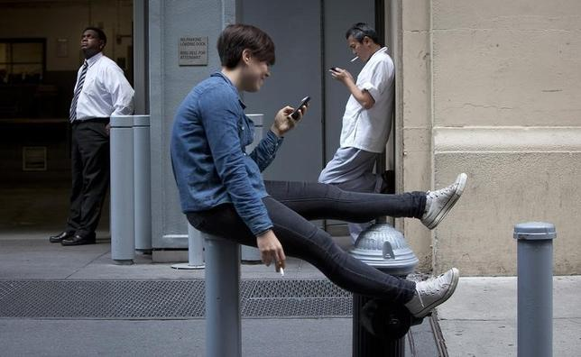 People smoke during a break outside an office building in midtown New York September 3, 2013.     REUTERS/Carlo Allegri