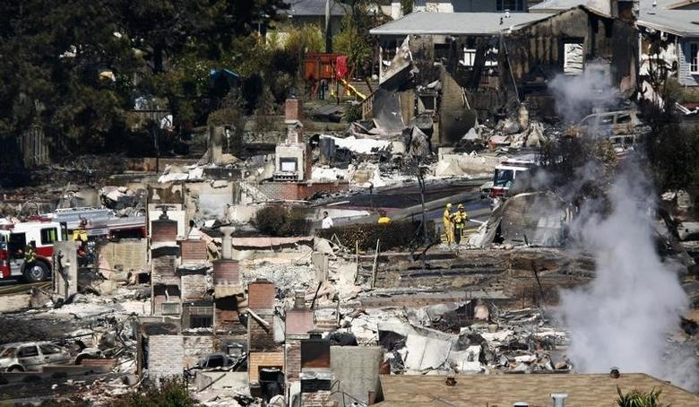 Firemen spray water on the remains of a house as smoke rises from the aftermath of Thursday's fiery gas line explosion in a neighborhood in San Bruno, California September 10, 2010. REUTERS/Ramin Rahimian