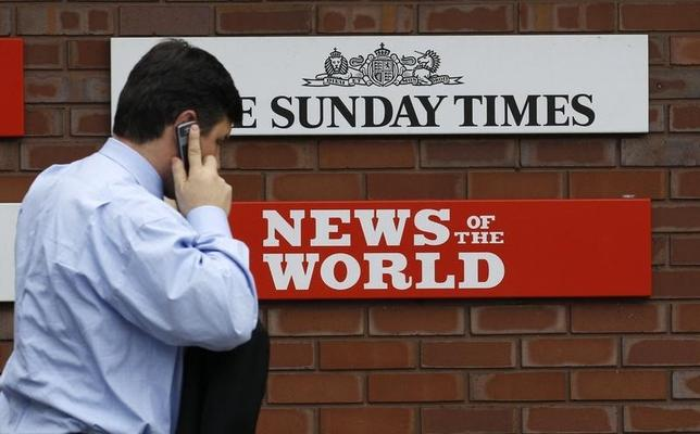 A man passes a sign outside the News International Limited complex, in London January 27, 2011.  REUTERS/Suzanne Plunkett