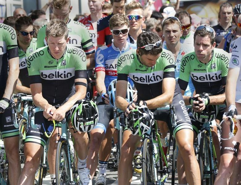 Riders of the Dutch cycling team Belkin wear black armbands and observe a minute of silence before departing on the 197.5km 13th stage of the Tour de France cycle race between Saint Etienne and Chamrousse, July 18, 2014.   REUTERS/Jean-Paul Pelissier