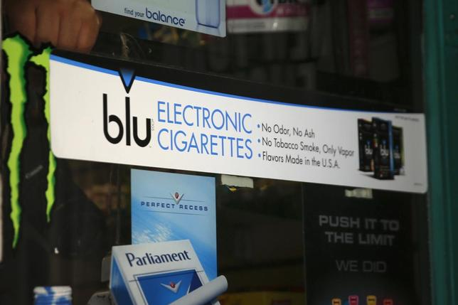 An advertisement for the e-cigarette brand blu is seen on the window of a store in New York in this file photo taken May 27, 2014. REUTERS/Shannon Stapleton/Files