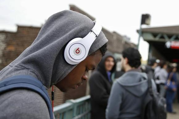 A commuter uses Beats brand headphones while waiting for the subway in New York May 29, 2014. REUTERS/Shannon Stapleton/Files