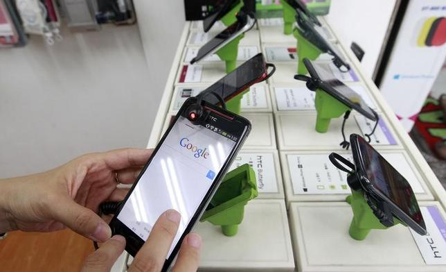 A customer tries out a HTC smartphone Butterfly S inside a mobile phone shop in Taipei July 30, 2013.  REUTERS/Pichi Chuang