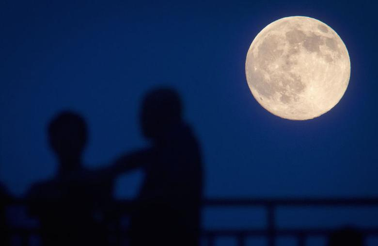 People stand and look at the moon one day ahead of the Supermoon phenomenon from a bridge over 42nd St. in the Manhattan borough of New York July 11, 2014.   REUTERS/Carlo Allegri