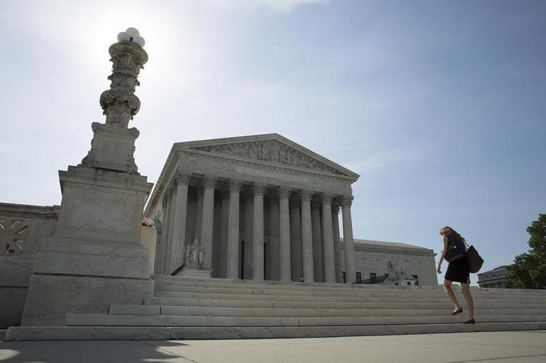A woman walks to the Supreme Court in Washington June 19, 2014.     REUTERS/Joshua Roberts