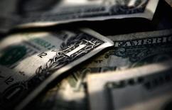 Долларовые купюры в Торонто 26 марта 2008 года. Ориентированные на РФ фонды испытывают вывод средств шестую неделю подряд, но за последние 7 дней отток оказался самым скромным, а денежные поступления из фондов GEM слегка поддержали российские акции. REUTERS/Mark Blinch