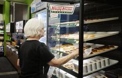 Imagen de archivo de una mujer comprando donas Krispy Kreme al interior de una tienda de la cadena WalMart en Bentonville, EEUU, jun 5 2014. El gasto del consumidor estadounidense creció por quinto mes consecutivo en junio, pero una moderación de los aumentos de precios, reflejada en un subíndice de los datos de gastos, no ofreció argumentos como para que la Reserva Federal suba pronto las tasas de interés.   REUTERS/Rick Wilking