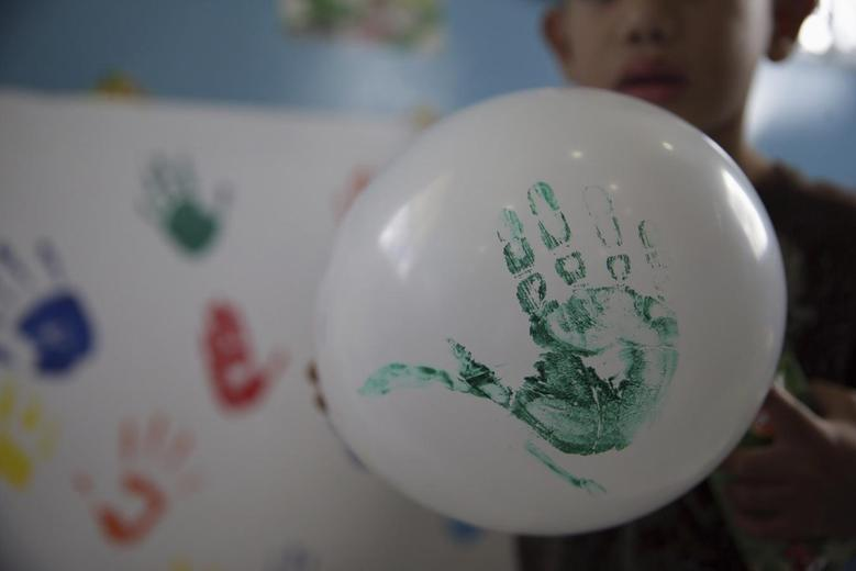 A child deported from the U.S. plays with a balloon after his arrival to the Ramon Villeda international airport in San Pedro Sula, in this July 18, 2014 handout photo provided by the Honduran Presidential House.  REUTERS/Honduran Presidential House/Handout via Reuters