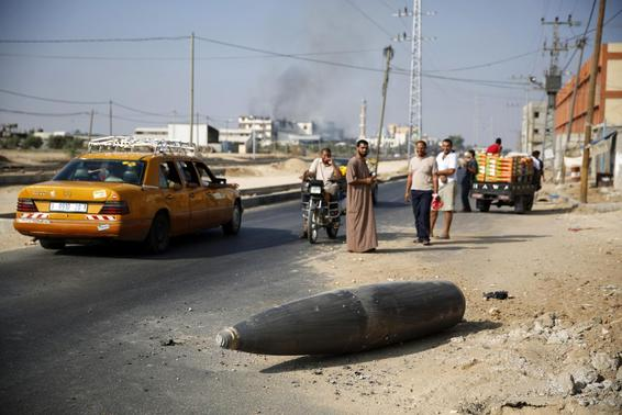 Palestinians look at an unexploded Israeli shell that landed on the main road outside the town of Deir Al-Balah in the central Gaza Strip August 1, 2014. REUTERS-Finbarr O'Reilly
