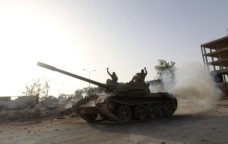 Fighters from the Benghazi Shura Council, which includes former rebels and militants from al Qaeda-linked Ansar al-Sharia, gesture on top of a tank next to the camp of the special forces in Benghazi July 30, 2014. REUTERS/Stringer