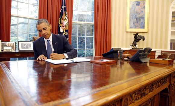 U.S. President Barack Obama signs into law S. 517, Unlocking Consumer Choice and Wireless Competition Act, in the Oval Office at the White House in Washington, August 1, 2014.     REUTERS/Larry Downing