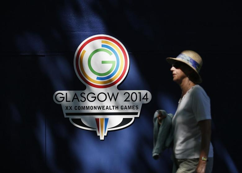 A spectator walks past the Commonwealth Games logo at the Kelvingrove Lawn Bowls Centre in Glasgow, Scotland, July 24, 2014. REUTERS/Jim Young