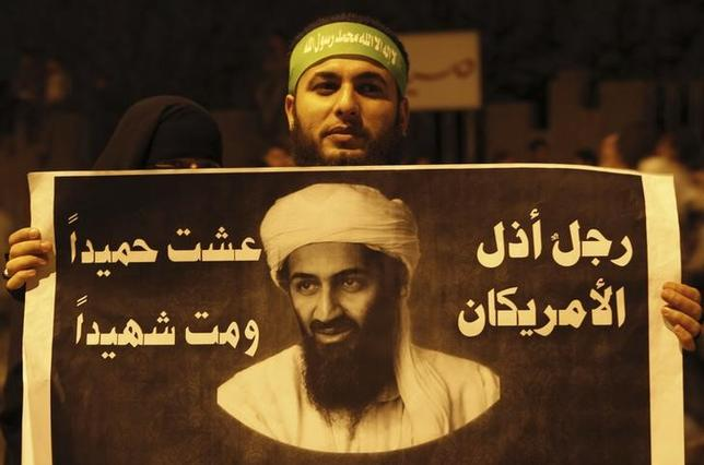 A couple of Islamist protesters hold up a poster with a picture of Osama bin Laden that reads, ''Man humiliated Americans. He lives benign and died a martyr'' during a protest march at the main entrance of the state security headquarters in Cairo May 2, 2013. REUTERS/Amr Abdallah Dalsh/Files