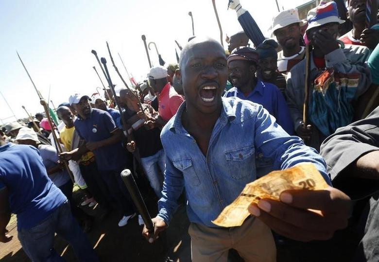 Striking platinum miners sing and dance during a rally near Lonmin's Marikana mine April 29, 2014.  REUTERS/Mike Hutchings
