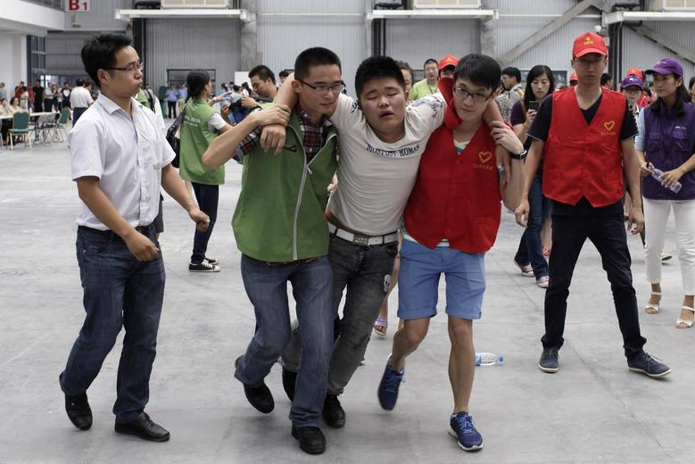 Volunteers carry a man (C) after he fainted at a caring centre for relatives of victims of a factory explosion, in Kunshan, Jiangsu province August 3, 2014. REUTERS/Stringer