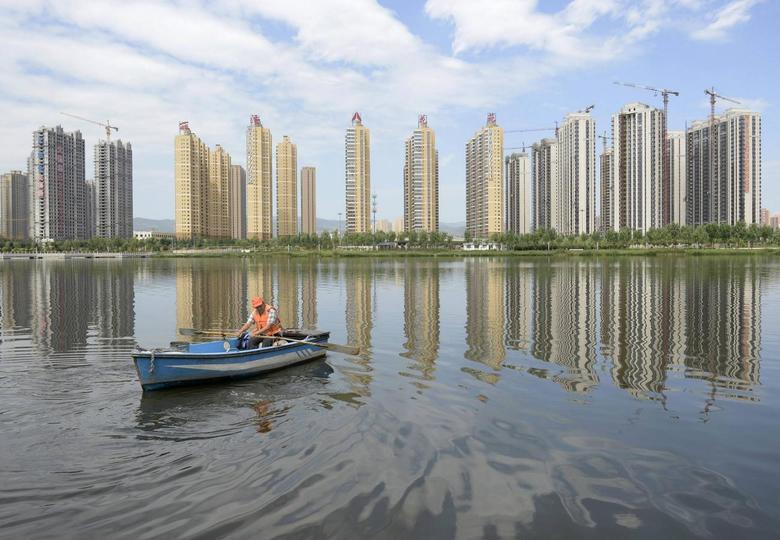 A man rows a boat on a river in front of new properties in Taiyuan, Shanxi province, July 24, 2014.  REUTERS/Stringer