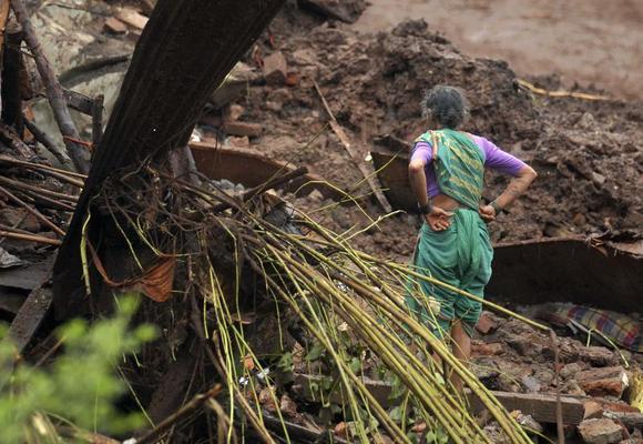 A resident looks at the debris of her damaged house after a landslide at Malin village in Maharashtra July 30, 2014. REUTERS/Stringer