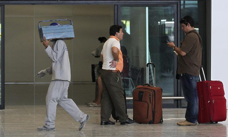 A worker walks past passengers at Manaus airport in Manaus June 2, 2014. REUTERS/Bruno Kelly/Files