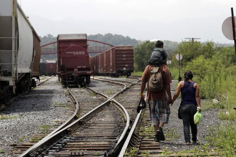 A couple from El Salvador walk with their three-year old son on the train tracks in Saltillo August 4, 2014.  REUTERS/Daniel Becerril