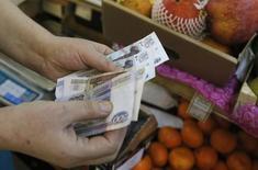 Торговка считает рубли на рынке в Москве 3 марта 2014 года. Деловая активность в секторе услуг РФ сократилась в июле 2014 года на фоне наиболее масштабных сокращений персонала за последние пять лет и вопреки небольшому приросту новых заказов, свидетельствует исследование, проведенное Markit по заказу HSBC. REUTERS/Maxim Shemetov