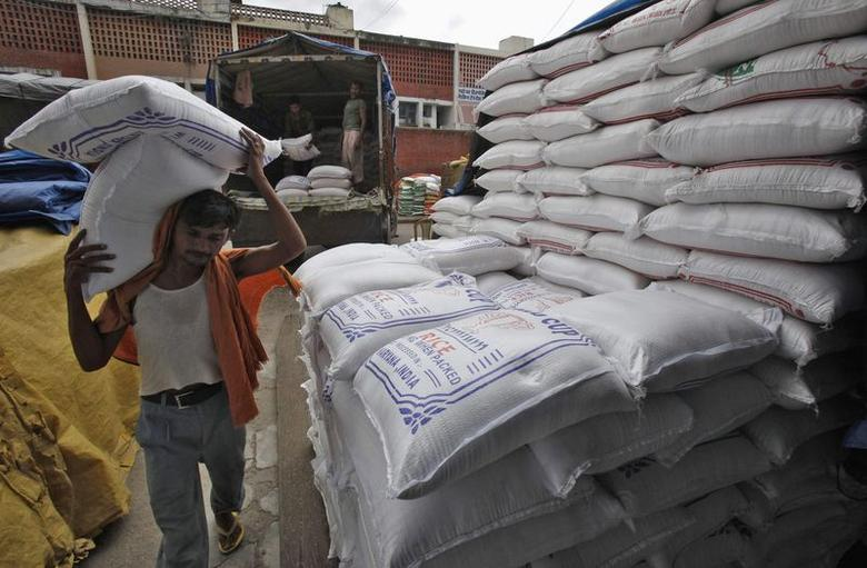 A labourer unloads sacks filled with rice at a wholesale grain market in Chandigarh July 29, 2014. REUTERS/Ajay Verma/Files