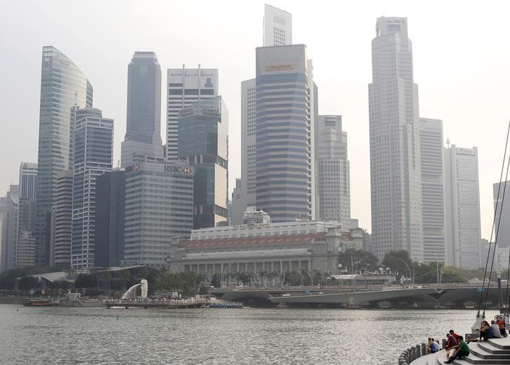 People sit along the Marina Bay area in the hazy skyline of Singapore March 4, 2014.  REUTERS/Edgar Su