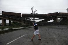 Мужчина идет мимо разрушенного железнодорожного моста в Новобахмутовке 7 июля 2014 года. Украина, вторая по размеру экономика на постсоветском пространстве, теряет прибыльные экспортные заказы на стальную продукцию из-за продолжающихся на востоке страны военных действий, вызвавших серьезные перебои в грузовых потоках по железной дороге. REUTERS/Maxim Zmeyev