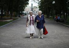 Женщины прогуливаются по Гоголевскому бульвару в Москве 17 августа 2013 года. Правительство РФ приняло решение продлить на 2015 год мораторий на формирование накопительной части пенсий, сообщило во вторник Министерство труда. REUTERS/Lucy Nicholson