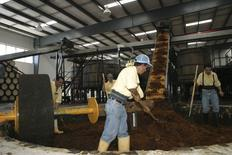 Workers at the Patron distillery move crushed agave to the fermentation vats as the huge donut-shaped tahona stone rests, in Atotonilco, Jalisco, in this undated handout photo courtesy of Patron Spirits Company. REUTERS/Patron Spirits Company/Handout via Reuters