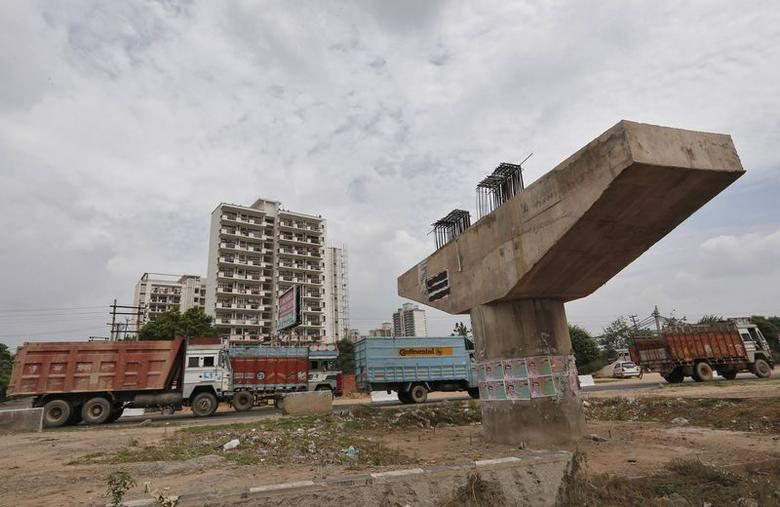 Vehicles travel past a Delhi-Jaipur national highway flyover under construction at Manesar in Haryana, July 24, 2014.  REUTERS/Adnan Abidi