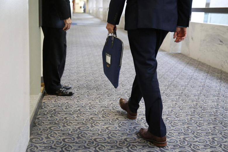 A U.S. Senate Intelligence Committee staff member enters the committee's offices with a secure attache case on Capitol Hill in Washington July 31, 2014.  REUTERS/Jonathan Ernst