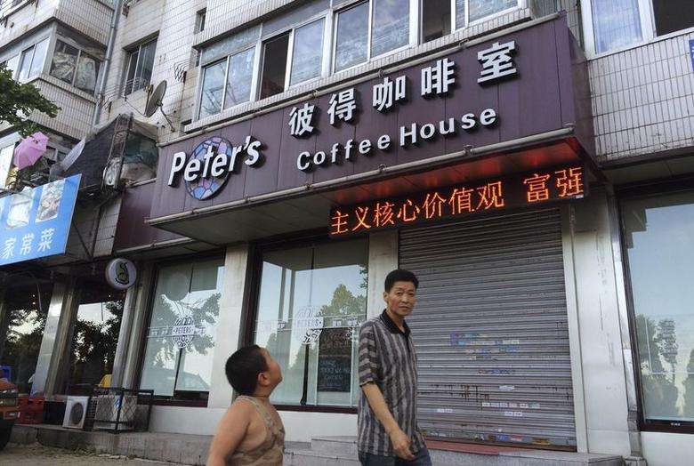 A boy looks up as he walks past the closed coffee shop owned by Canadian couple Kevin Garratt and Julia Dawn Garratt in Dandong, Liaoning province, August 5, 2014.REUTERS/Ben Blanchard