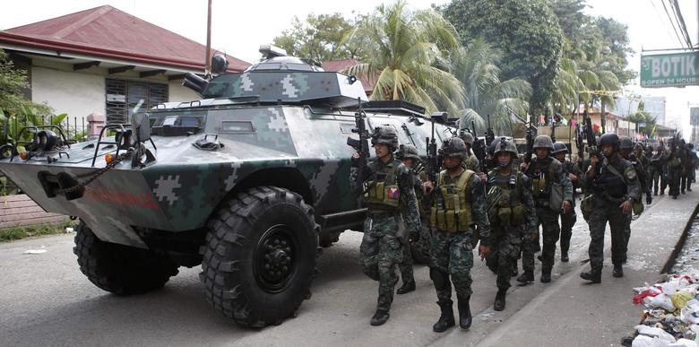 Members of the elite Special Action Police walk next to an armoured vehicle as they reinforce soldiers battling Muslim rebels from the Moro National Liberation Front (MNLF) in Zamboanga city, in southern Philippines in this September 12, 2013 file photo.  REUTERS/Erik De Castro/Files