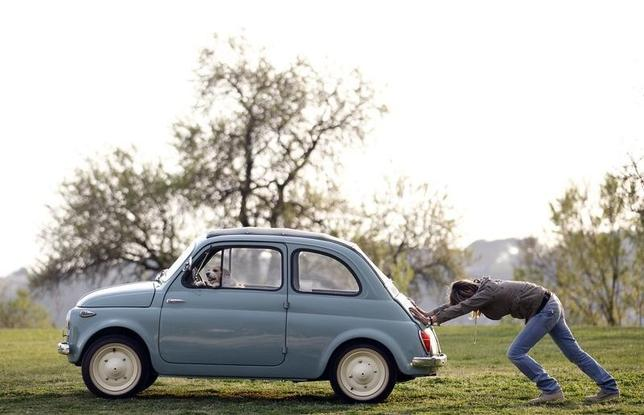 A woman pushes her Fiat 500 car as her dog sits inside, in a neighbourhood of Rome March 23, 2012.   REUTERS/Alessandro Bianchi