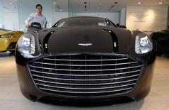 Sales Manager Raymond Liu switches on the headlights of an Aston Martin Vanquish at their showroom in Singapore August 1, 2014. REUTERS/Edgar Su