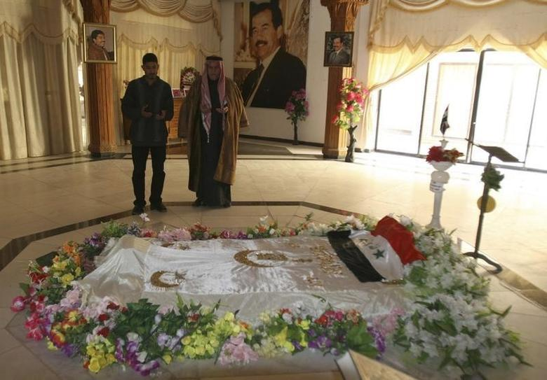Residents pray near the tomb of executed former Iraqi President Saddam Hussein in Awja, December 3, 2008.  REUTERS/Sabah al-Bazee