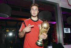 Germany's Mario Goetze poses with the World Cup trophy during the DFB-WM gala party at the Sheraton hotel in Rio de Janeiro July 13, 2014. Germany are champions of the world again after snatching victory against Argentina in the World Cup final soccer match. Picture taken July 13. REUTERS/Markus Gilliar/Pool (BRAZIL - Tags: SPORT SOCCER WORLD CUP)