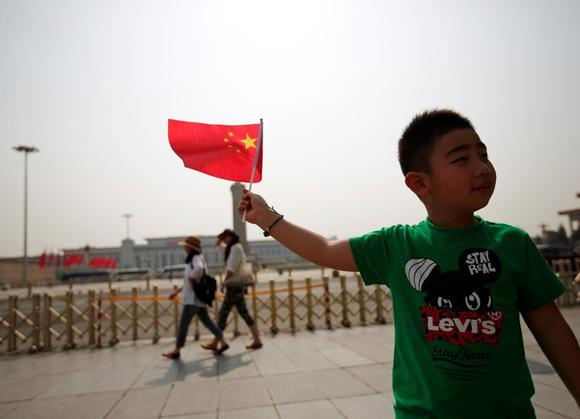 A boy poses with a Chinese national flag in front of Tiananmen Square in Beijing June 4, 2014. REUTERS/Kim Kyung-Hoon/Files