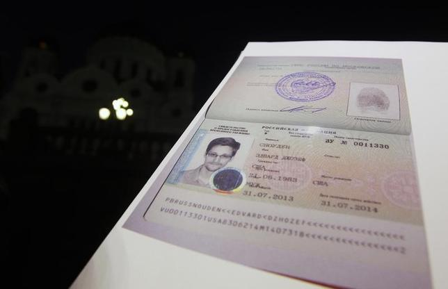 Fugitive former U.S. spy agency contractor Edward Snowden's refugee documents granted by Russia is seen during a news conference in Moscow August 1, 2013.   REUTERS/Maxim Shemetov