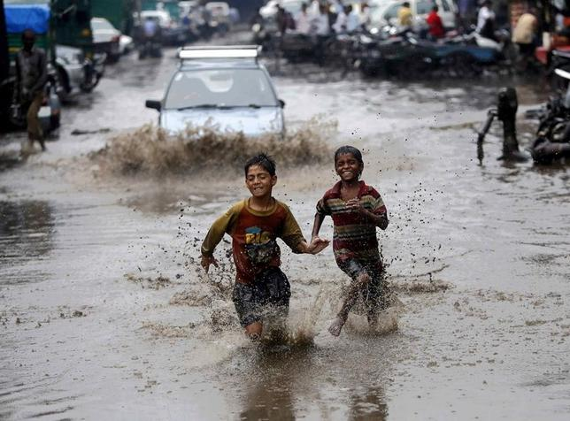 Boys run through a water logged street after heavy monsoon rains in New Delhi August 2, 2014. REUTERS/Anindito Mukherjee/Files