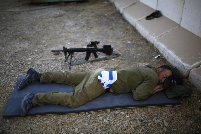 An Israeli soldier sleeps at a military post just outside the border with the Gaza Strip August 7, 2014.  REUTERS/ Amir Cohen