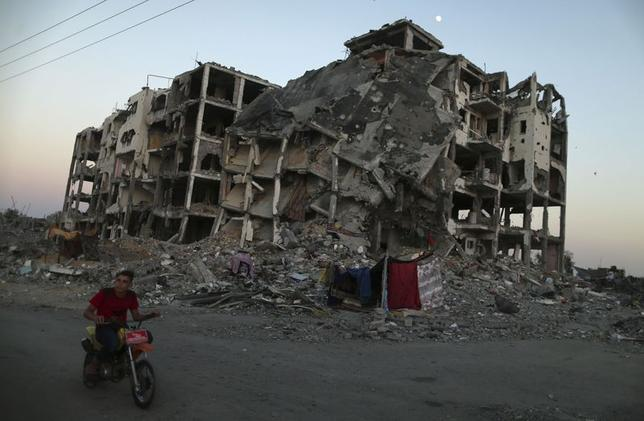 A Palestinian rides past residential buildings in Beit Lahiya town, which witnesses said was heavily hit by Israeli shelling and air strikes during the Israeli offensive, in the northern Gaza Strip August 7, 2014. REUTERS/Mohammed Salem